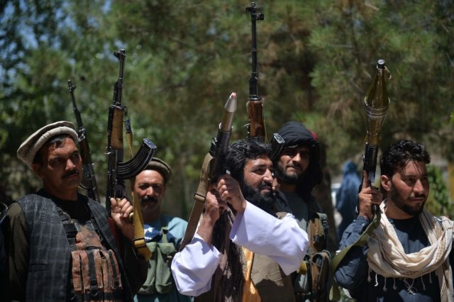 Afghans gather with their heavy weapons to support government security forces against the Taliban, in Guzara district, Herat province