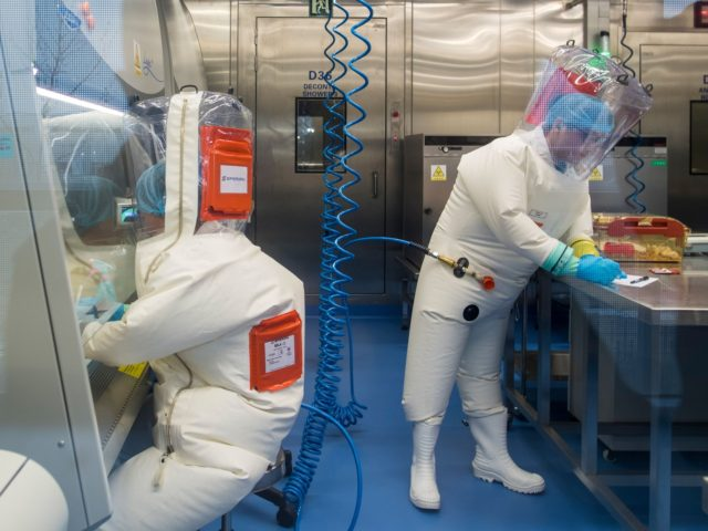 Workers are seen next to a cage with mice (R) inside the P4 laboratory in Wuhan, capital of China's Hubei province, on February 23, 2017. - The P4 epidemiological laboratory was built in co-operation with French bio-industrial firm Institut Merieux and the Chinese Academy of Sciences. (Photo by Johannes EISELE …