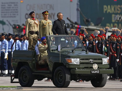 Pakistani President Arif Alvi, stands in a black suit on a military vehicle while reviewing a military parade in connection with Pakistan National Day celebrations, in Islamabad, Pakistan, Thursday, March 25, 2021. The military parade in the capital showcased short and long-range missiles, tanks, jets drones and other hardware. (AP …