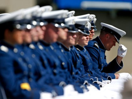 A graduating Air Force Academy cadet straightens his cap during the graduation ceremony for the class of 2015, at the U.S. Air Force Academy, in Colorado Springs, Colo., Thursday, May 28, 2015. (AP Photo/Brennan Linsley)