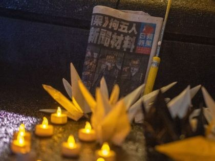 A copy of Hong Kong's pro-democracy Apple Daily newspaper is seen during a vigil following a march in protest against the 100th anniversary of the founding of the Communist Party of China, in Tokyo's Shinjuku district on July 1, 2021. (Photo by Philip FONG / AFP) (Photo by PHILIP FONG/AFP …