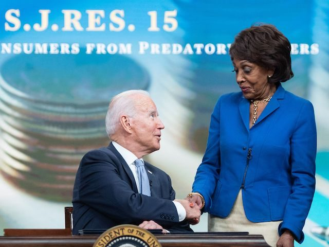 US President Joe Biden sits alongside Speaker of the House Nancy Pelosi (L), Representative Chuy Garcia (R), (D-IL), and Representative Maxine Waters (2nd R), (D-CA), prior to signing S.J. Res. 15, a bill dealing with predatory lending practices, into law during a ceremony in the Eisenhower Executive Office Building in …