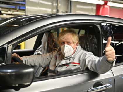 """Britain's Prime Minister Boris Johnson gives a thumbs up as he tours Japanese auto giant Nissan's production plant in Sunderland, north east England on July 1, 2021. - Nissan today announced plans to build the UK's first car-battery """"gigafactory"""", where it will build a new electric vehicle. (Photo by Jeff …"""
