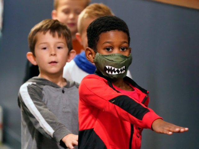 Students waking in the hallway at Tibbals Elementary School place their arms in front as a reminder to socially distance in Murphy, Texas, Thursday, Dec. 3, 2020. Texas Gov. Greg Abbot's statewide mask order does not mandate face covering for children under the age of 10, allowing some school districts …