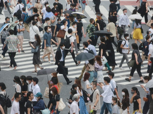 People wearing face masks to protect against the spread of the coronavirus cross a street in Tokyo, Wednesday, July 28, 2021. Tokyo Gov. Yuriko Koike on Wednesday urged younger people to cooperate with measures to bring down the high number of infections and get vaccinated, saying their activities are key …