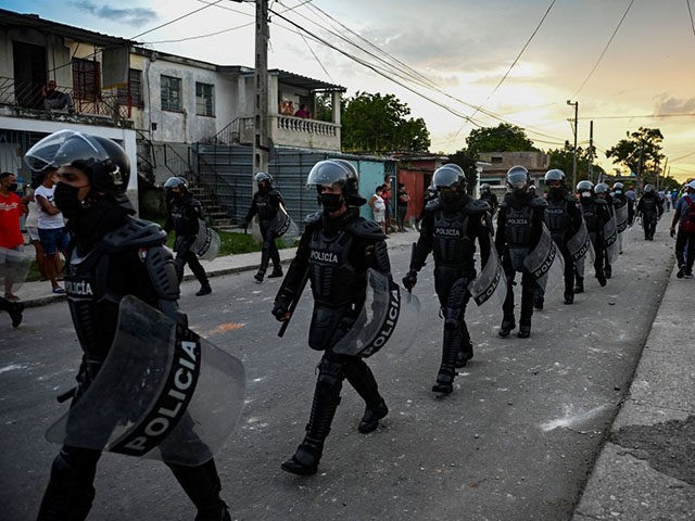 """TOPSHOT - Riot police walk the streets after a demonstration against the government of President Miguel Diaz-Canel in Arroyo Naranjo Municipality, Havana on July 12, 2021. - Cuba on Monday blamed a """"policy of economic suffocation"""" of United States for unprecedented anti-government protests, as President Joe Biden backed calls to …"""