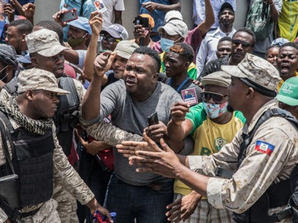 Police try to hold people back as supporters cheer and surround an ambulance carrying former Haitian President Jean-Bertrand Aristide after he arrived at the airport in Port-au-Prince on July 16, 2021, after spending nearly a month in Cuba for medical treatment. (Photo by Valerie Baeriswyl / AFP) (Photo by VALERIE …
