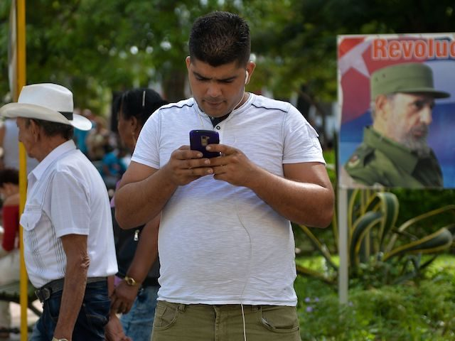 TOPSHOT - A man connects to internet from his mobile phone in Havana, on March 17, 2019, with a sign depicting Cuban late leader Fidel Castro in the background. - A new civil society emerges in Cuba with mobile phones having internet, defying six decades of unanimity. (Photo by YAMIL …