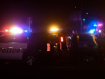 TOPSHOT - Police officers are seen at the intersection of US 101 freeway and the Moorpark Rad exit as police vehicles close off the area responding to a shooting at a bar in Thousand Oaks, California on November 8, 2018. - Twelve people, including a police sergeant, were shot dead …
