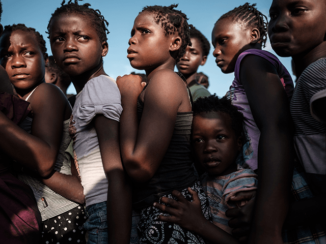 Children wait in line to receive food distribution from a local supermarket at an evacuation center in Dondo, about 35km north from Beira, Mozambique, on March 27, 2019. - Five cases of cholera have been confirmed in Mozambique following the cyclone that ravaged the country killing at least 468 people, …