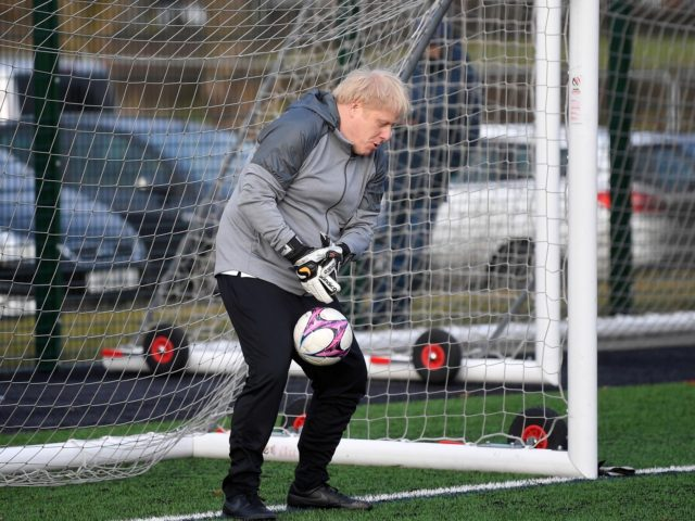 Britain's Prime Minister Boris Johnson tries to save a shot during a warm up before a girls football match while on the campaign trail in Cheadle Hulme, northwest England on December 7, 2019. - Britain will go to the polls on December 12, 2019 to vote in a pre-Christmas general …
