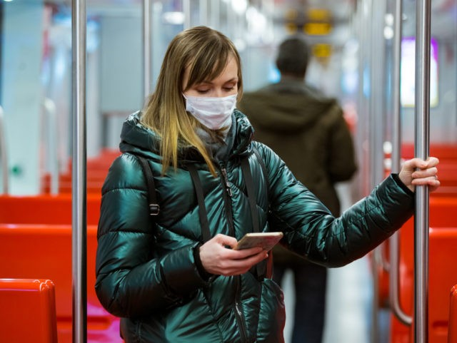 Woman in winter coat with protective mask on face standing in subway car, using phone, looking worried. Preventive measures in public places of epidemic regions. Finland, Espoo