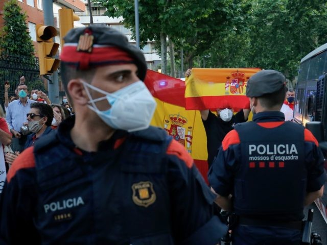 Demonstrators hold up Spanish flags in front of police, during a protest on May 20, 2020, in Barcelona, against the Spanish government's measures during the national lockdown to prevent the spread of the COVID-19 disease. - Renewed four times, the state of emergency has let the government impose some of …