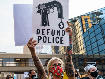"""A Protester hold a sign reading """"Defund the Police"""" outside Hennepin County Government Plaza during a demonstration against police brutality and racismon August 24, 2020 in Minneapolis, Minnesota. - It was the second day of demonstrations in Kenosha after video circulated Sunday showing the shooting of Jacob Blake -- multiple …"""