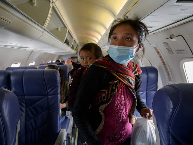 """TOPSHOT - Central Americ migrant Filomena boards a flight from McAllen to Houston at McAllen airport after being released from a US government holding facility for illegal migrants seeking asylum in McAllen, Texas. - """"Please help me, I don't speak English, """"a manila envelope reads in large black letters with …"""