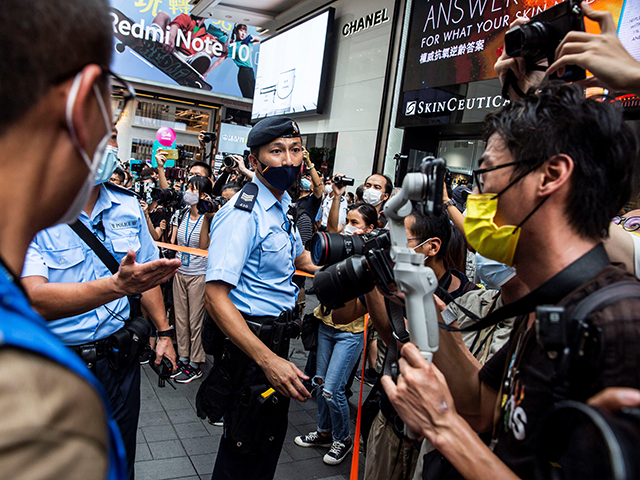 A police officer (C) uses tape to hold media back on the 24th anniversary of Hong Kong's handover from Britain, in Hong Kong on July 1, 2021. (Photo by ISAAC LAWRENCE / AFP) (Photo by ISAAC LAWRENCE/AFP via Getty Images)
