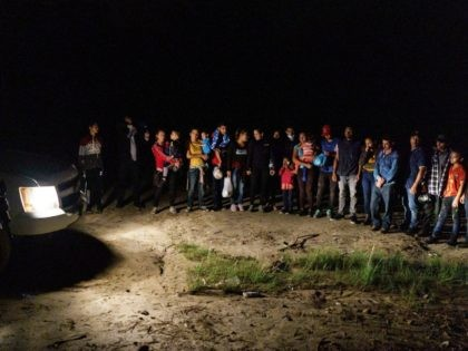 """Migrant families are lined up after crossing the US-Mexico border into the United States in Roma, Texas on July 9, 2021 - Republican lawmakers have slammed Biden for reversing Trump programs, including his """"remain in Mexico"""" policy, which had forced thousands of asylum seekers from Central America to stay south …"""