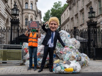 LONDON, ENGLAND - JULY 13: In this handout photo provided by Greenpeace, Greenpeace activists dump bags of plastic waste at the main entrance to Downing Street in a protest against the UK governments exporting of plastic waste on July 13, 2021 in London, England. 625 kilograms of plastic recycling has …