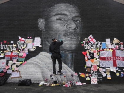 MANCHESTER, ENGLAND - JULY 13: The artist known as AKSE_P19, who painted the mural of England footballer Marcus Rashford which is displayed on the wall of a cafe on Copson Street, Withington, sets about repairing it after it was defaced by vandals in the aftermath of England's Euros loss on …