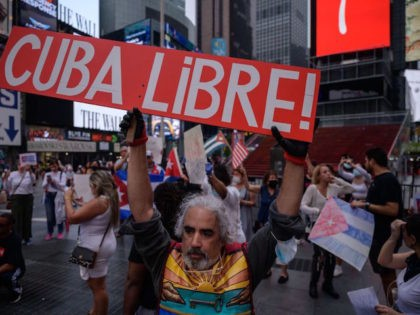 TOPSHOT - Demonstrators hold placards during a rally held in solidarity with anti-government protests in Cuba, in Times Square, New York on July 13, 2021. - One person died and more than 100 others, including independent journalists and dissidents, have been arrested after unprecedented anti-government protests in Cuba, with some …