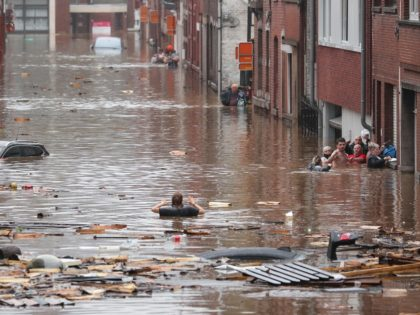 TOPSHOT - A woman is trying to move in a flooded street following heavy rains in Liege, on July 15, 2021. Illustration shows the scene in Liege after heavy rainfall, Thursday 15 July 2021. - The provincial disaster plan has been declared in Liege, Luxembourg and Namur provinces after large …