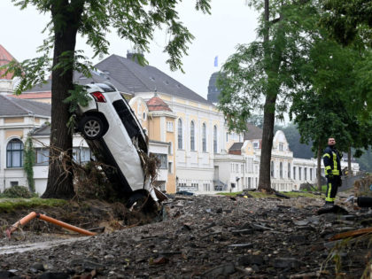 A fireman stands next to a destroyed car pressed against a tree by the torrents after the floods caused major damage in Bad Neuenahr-Ahrweiler, western Germany, on July 16, 2021. - The death toll from devastating floods in Europe soared to at least 118 on July 16, with at least …
