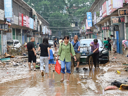 A woman carries a bag on a muddy street after severe flooding and landslide in recent days have hit the county-level Gongyi city, near Zhengzhou, in central Chinas Henan province on July 22, 2021. (Photo by JADE GAO / AFP) (Photo by JADE GAO/AFP via Getty Images)