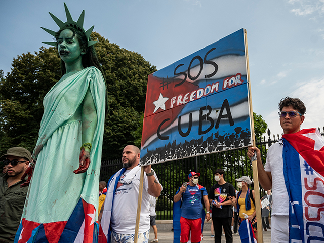 A protester dresses as the Statue of Liberty as others wear Cuban flags during a demonstration in front of the White House in Washington DC, on July 25, 2021. - Rallies are taking place around the world as Cuba endures its worst economic crisis in 30 years, with chronic shortages …