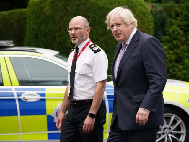 Britain's Prime Minister Boris Johnson (R) walks with Chief Constable Gavin Stephens (L) during a visit to Surrey Police headquarters in Guildford, south west of London, on July 27, 2021 to coincide with the publication of the government's plans to tackle crime. (Photo by Yui Mok / POOL / AFP) …