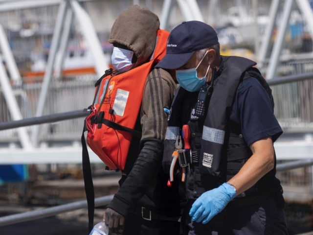 DOVER, ENGLAND - JUNE 24: Border Force officials guide newly arrived migrants to a holding facility after being picked up in a dinghy in the English Channel on June 24, 2021 in Dover, England. More than 5,000 migrants have arrived this year by crossing the English Channel in boats. (Photo …