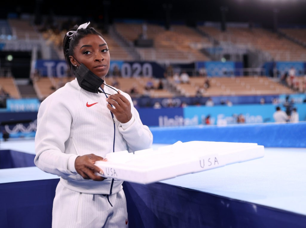 Simone Biles of Team United States supports her team mates by carrying their chalk after pulling out after the vault during the Women's Team Final on day four on day four of the Tokyo 2020 Olympic Games at Ariake Gymnastics Centre on July 27, 2021 in Tokyo, Japan. (Photo by Laurence Griffiths/Getty Images)