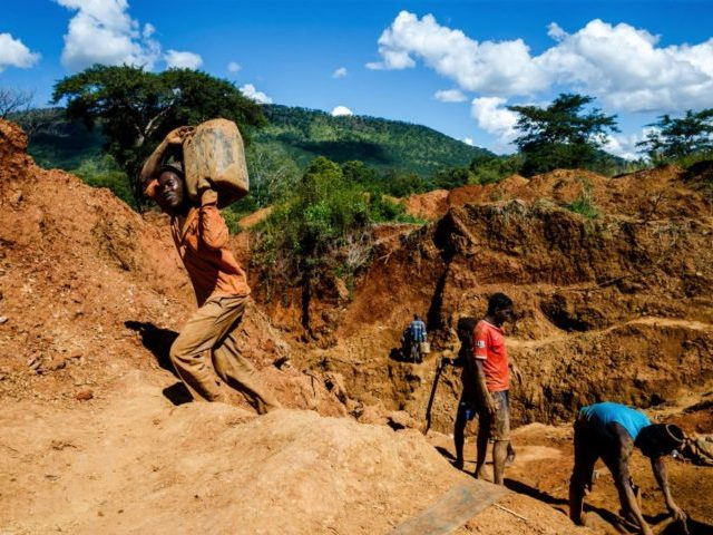A miner carries a load of ore at Manzou Farm, owned by Grace Mugabe, wife of former Zimbabwean President Robert Mugabe, in Mazowe, Zimbabwe on April 5, 2018. Local media reported on March 30, 2018 that illegal gold miners in Zimbabwe have seized a farm belonging to former first lady …
