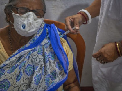 A health worker inoculates an elderly woman with a dose of the Covishield vaccine against the Covid-19 coronavirus at a temporary vaccination camp set up in Siliguri on July 28, 2021. (Photo by Diptendu DUTTA / AFP) (Photo by DIPTENDU DUTTA/AFP via Getty Images)