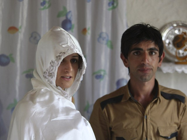 In this picture taken on Friday, July 15, 2011, Iranian bride Maryam Sadeghi, stands with groom Javad Jafari, as they pose for photographs before Javad wears his formal wedding dress, during their wedding, at the Ghalehsar village about 220 miles (360 kilometers) northeast of the capital Tehran, Iran. (AP Photo/Vahid …