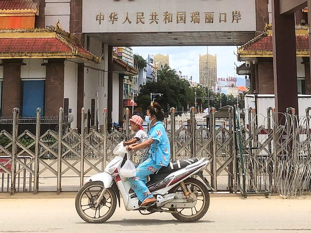 A woman rides a scooter with a child past the China-Myanmar border gate in Muse in Shan state on July 5, 2021, as the Chinese city of Ruili near the border with Myanmar imposed a lockdown and started mass testing after three Covid-19 coronavirus cases were reported on Monday. (Photo …