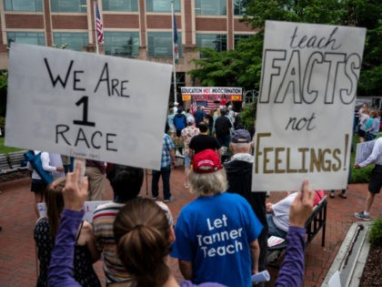 """People hold up signs during a rally against """"critical race theory"""" (CRT) being taught in schools at the Loudoun County Government center in Leesburg, Virginia on June 12, 2021. - """"Are you ready to take back our schools?"""" Republican activist Patti Menders shouted at a rally opposing anti-racism teaching that …"""
