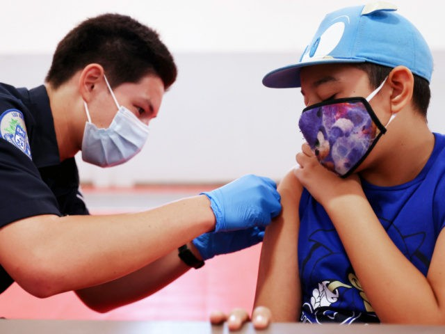 WINNETKA, CALIFORNIA - JULY 06: EMT Quentin Scarborough applies an adhesive bandage after administering a vaccine dose to student Nathan Alex Perez during a pop-up COVID-19 vaccination clinic at James Jordan Middle School on July 6, 2021 in Winnetka, California. The clinic was hosted by the Fernandeno Tataviam Band of …