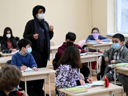 Schoolchildren wearing face masks listen to a teacher at a school in Tbilisi on February 15, 2021, as in-person classes resume in Georgian schools amid the ongoing coronavirus disease pandemic. (Photo by Vano Shlamov / AFP) (Photo by VANO SHLAMOV/AFP via Getty Images)
