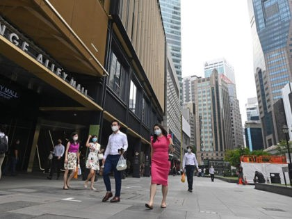 People walk during lunch time at the Raffles Place financial business district in Singapore on February 16, 2021. (Photo by Roslan RAHMAN / AFP) (Photo by ROSLAN RAHMAN/AFP via Getty Images)