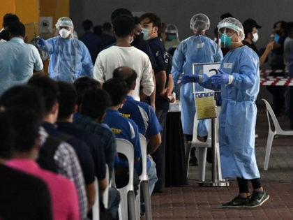 Essential workers wait to take a nasal swab test to detect the COVID-19 novel coronavirus before returning to work in Singapore on June 10, 2020. (Photo by Roslan RAHMAN / AFP) (Photo by ROSLAN RAHMAN/AFP via Getty Images)