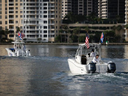 Boats with Cuban and US flags part of a Cuban support flotilla depart from Bayside in downtown Miami for Cuba, on July 23, 2021. - The flotilla plans to stay in international waters off Cuba to let island residents know they have support in Florida. (Photo by Eva Marie UZCATEGUI …