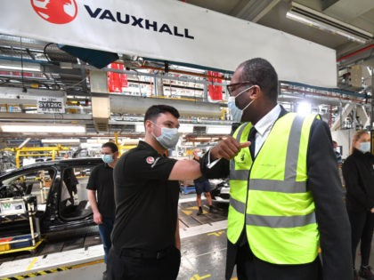 ELLESMERE PORT, ENGLAND - JULY 06: Kwasi Kwarteng, Secretary of State for Business, Energy and Industrial Strategy, meets graduate Oliver Holden on the production line ahead of a press conference announcing Stellantis' investment in the Vauxhall Ellesmere Port plant to build new electric vehicles, on July 06, 2021 in Ellesmere …