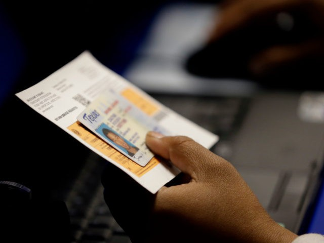 In this Feb. 26, 2014, file photo, an election official checks a voter's photo identification at an early voting polling site in Austin, Texas. A judge has ruled for a second time that Texas' strict voter ID law was intentionally crafted to discriminate against minorities. (AP Photo/Eric Gay, File)