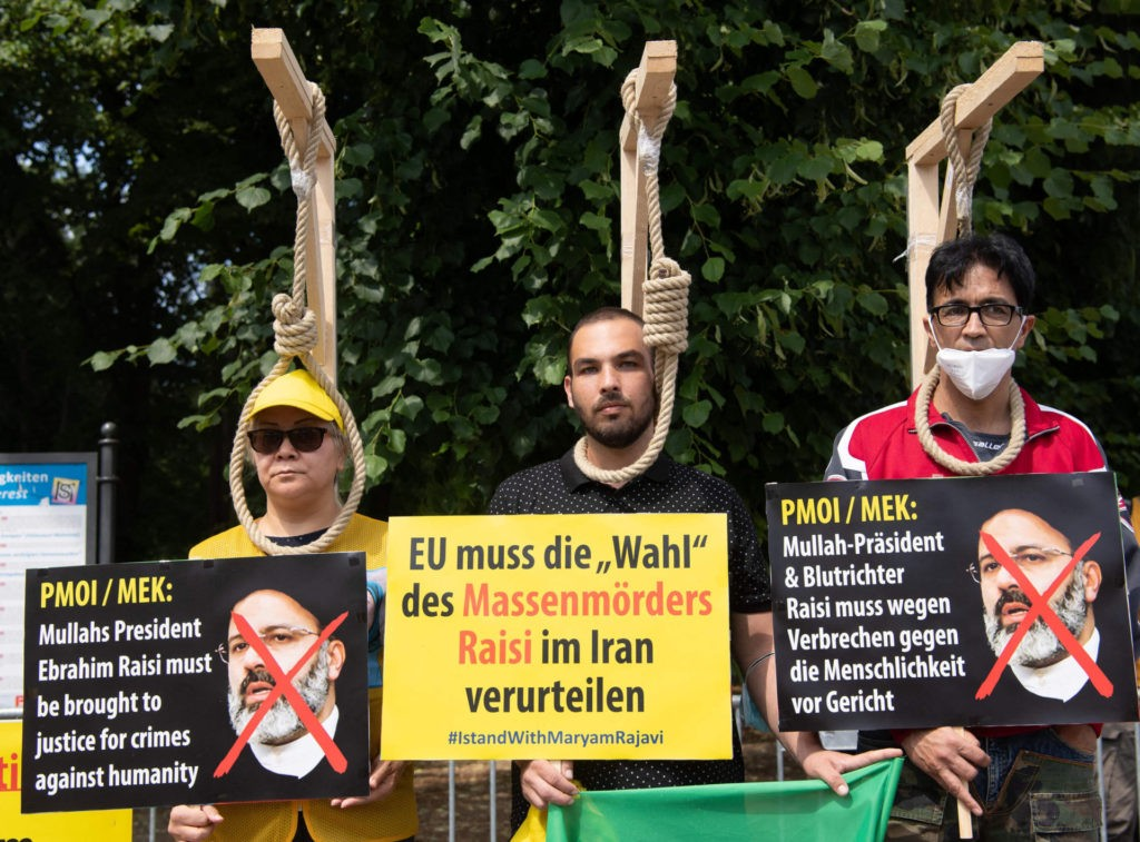 Demonstrators pose with mock-ups of gallows as they take part in a protest called by the National Council of Resistance of Iran (NCRI) against the Iranian regime in front of the Brandenburg Gate in Berlin on July 10, 2021. - Demonstrators, among them supporters of the National Council Of Resistance of Iran (NCRI) and its leader Maryam Rajavi, gathered in front of the Brandenburg Gate in a protest against the current Iranian regime and on the occasion of the online Free Iran World Summit 2021, the NCRI's annual gathering, which is held from July 10 until 12. (Photo by PAUL ZINKEN / AFP) (Photo by PAUL ZINKEN/AFP via Getty Images)