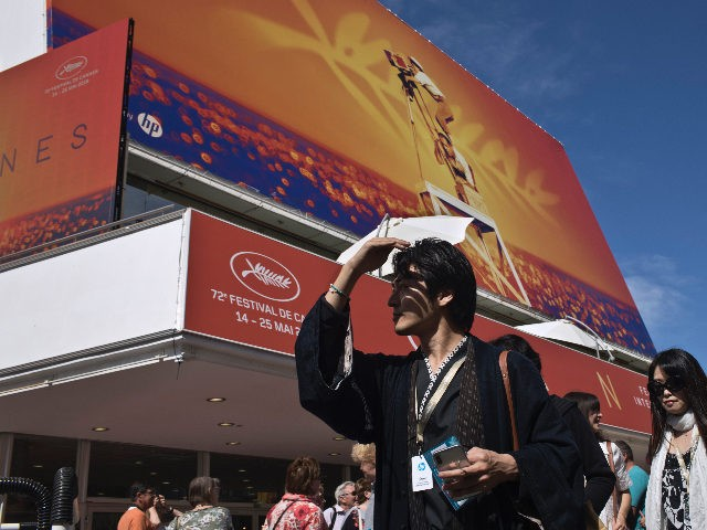 People walk by the Palais des festivals at the 72nd international film festival, Cannes, southern France, Monday, May 13, 2019. The Cannes film festival runs from May 14th until May 25th 2019. (AP Photo/Petros Giannakouris)