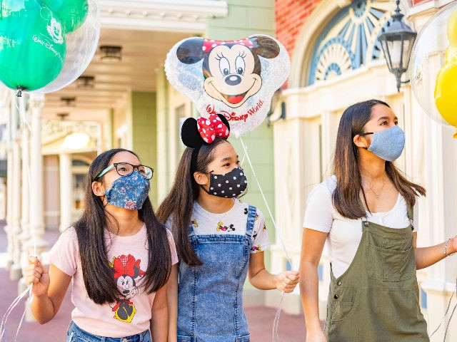 In this handout photo provided by Walt Disney World Resort, guests wear masks at Walt Disney World Resort on June 12, 2020 in Lake Buena Vista, Florida. All guests two years of age and older will be required to wear an appropriate face covering at all times, except when eating …