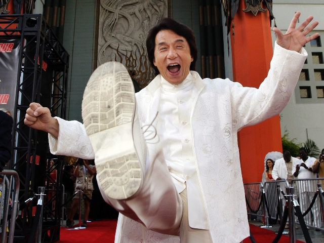 """Jackie Chan cast member of the film """"Rush Hour 3"""" throws a kick as he poses for photographers the premiere of the film at the Mann's Chinese Theater in the Hollywood section of Los Angeles, Monday July 30, 2007. (AP Photo/Kevork Djansezian)"""