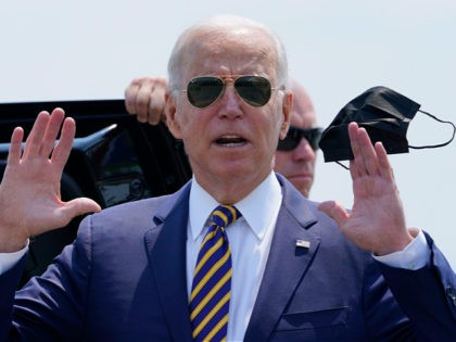 President Joe Biden holds a mask as he responds to a question as he arrives at Lehigh Valley International Airport in Allentown, Pa., Wednesday, July 28, 2021. Biden is in the area to visit the Lehigh Valley operations facility for Mack Trucks and advocate for government investments and clean energy …