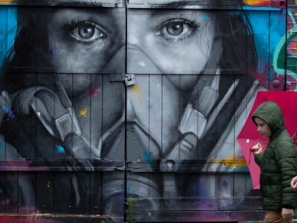 LONDON, ENGLAND - JUNE 11: A boy holding an umbrella walks past a mural of a woman wearing a mask in Shoreditch on June 11, 2020 in London, England. As the British government further relaxes Covid-19 lockdown measures in England, this week sees preparations being made to open non-essential stores …