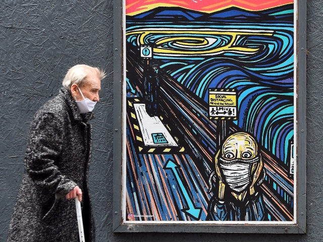 TOPSHOT - An elderly pedestrian wearing a face mask or covering due to the COVID-19 pandemic, walks past graffiti depicting the subjects within famous artworks, but wearing masks, in Glasgow on September 2, 2020 after the Scottish government imposed fresh restrictions on the city after an rise in cases of …